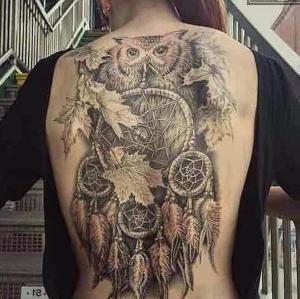 tatuaje en la espalda de buho y atrapasueños