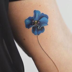 tatuaje delicado de flor azul
