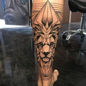 tatuaje geometrico de leon en la pierna