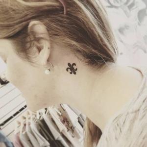 tatuaje en el cuello de flor de lis