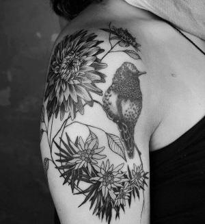 tatuaje de pajaro y flores en el hombro