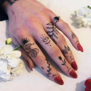 mujeres con los dedos de la mano tatuados