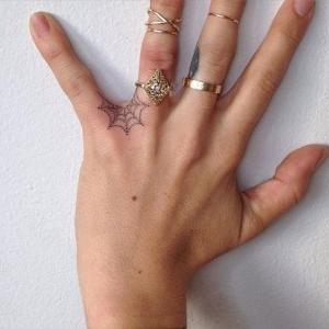 tatuaje pequeño de tela de arana en la mano