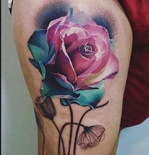 rosa a color tatuada en la pierna
